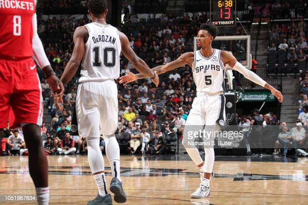 Dejounte Murray of the San Antonio Spurs exchanges high fives with his teammates against the Houston Rockets on October 7 2018 at ATT Center in San...