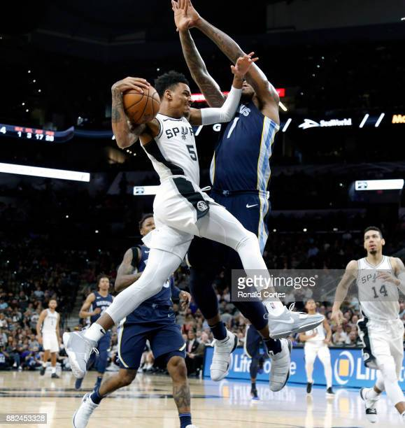 Dejounte Murray of the San Antonio Spurs is fouled by Jarell Martin of the Memphis Grizzlies as he drives to the basket at ATT Center on November 29...