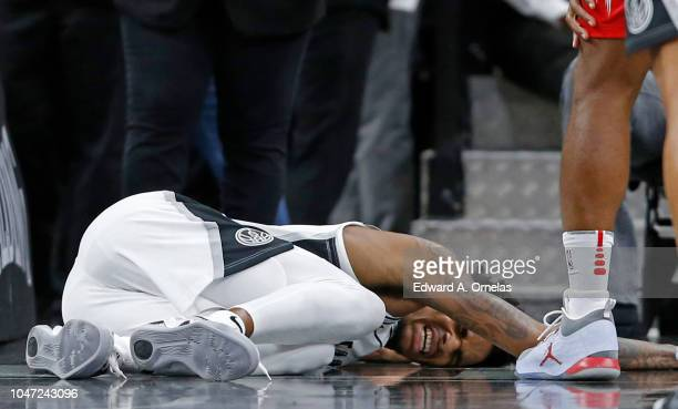 Dejounte Murray of the San Antonio Spurs reacts after being injured on a play during a preseason game against the Houston Rockets on October 7 2018...