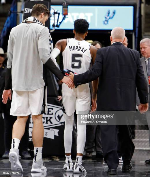 Dejounte Murray of the San Antonio Spurs walks off the court after being injured on a play as teammate Pau Gasol looks on during a preseason game...