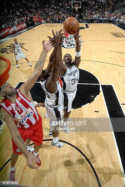 DeJuan Blair and Antonio McDyess of the San Antonio Spurs go up for the rebound against Ioannis Bourousis of the Greece Olympiacos during the...