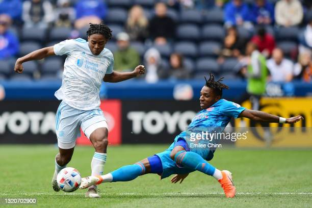 DeJuan Jones of New England Revolution and Joseph-Claude Gyau of FC Cincinnati compete for the ball during the second half at TQL Stadium on May 29,...