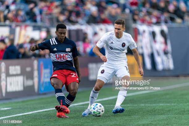 DeJuan Jones of New England Revolution passes the ball as Przemyslaw Frankowski of Chicago Fire defends during a game between Chicago Fire and New...