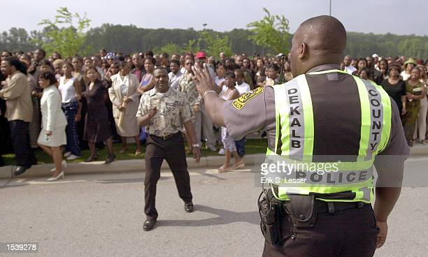 Dekalb County Police officer tries to control the thousands of fans waiting in line to attend the public funeral of singer Lisa Left Eye Lopes at the...