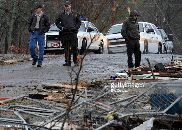 DeKalb County Sheriff's Deputies stand watch next to a log home which was destroyed by a tornado in the early morning hours on November 30 2016 in...