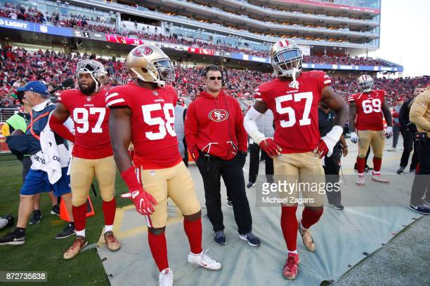 Dekoda Watson Elvis Dumervil Defensive Line Coach Jeff Zgonina and Eli Harold of the San Francisco 49ers stand on the sideline during the game...