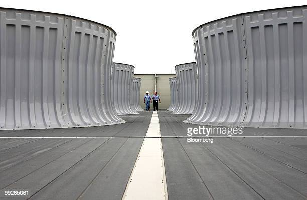 Del Carter left and Terry Smith walk past the eight cooling tower fans on the Central Plant roof in Sacramento California US on Monday April 26 2010...