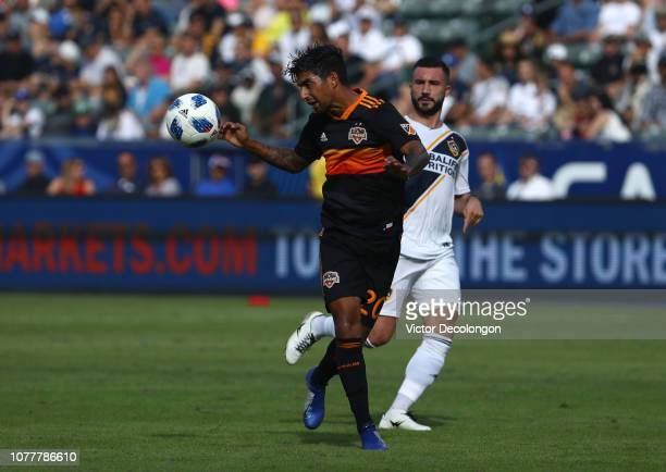 A J DeLaGarza of Houston Dynamo heads the ball clear of the box as Romain Alessandrini of Los Angeles Galaxy during the second half of the MLS match...