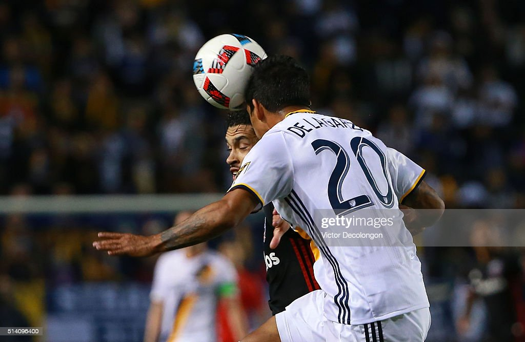 A. J. DeLaGarza #20 of Los Angeles Galaxy heads the ball clear from Lamar Neagle #13 of D.C. United in the first half of their MLS match at StubHub Center on March 6, 2016 in Carson, California.