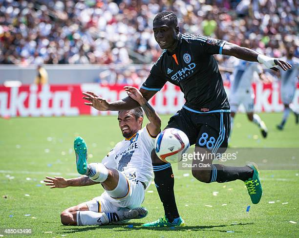 AJ DeLaGarza of Los Angeles Galaxy makes a tackle as Kwadwo Poku of New York City FC races in on goal during Los Angeles Galaxy's MLS match against...