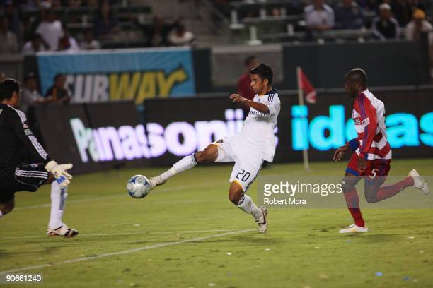 J DeLaGarza of the Los Angeles Galaxy attempts a shot past goalkeeper Dario Sala and Jair Benitez of FC Dallas during their MLS game at The Home...