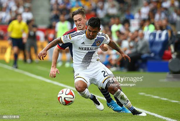 J DeLaGarza of the Los Angeles Galaxy holds off a challenge for the ball by Kelyn Rowe of the New England Revolution in the second half during 2014...