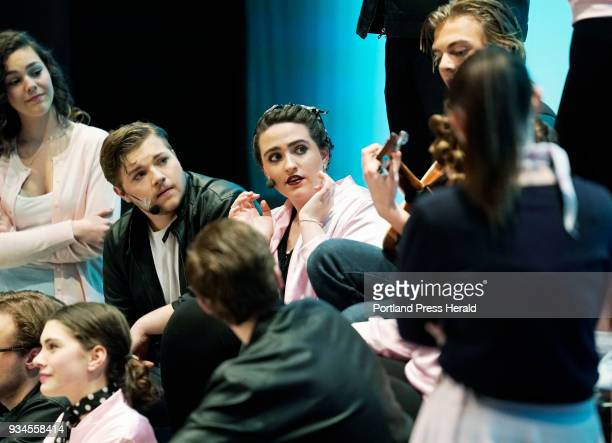Delaney Bailey center playing the role of Betty Rizzo listens with Tyler McDonnell to her left in the role of Kenickie and other cast memebers as...