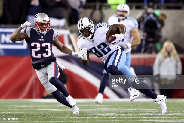 Delanie Walker of the Tennessee Titans carries the ball after catching a pass as he is defended by Patrick Chung of the New England Patriots in the...