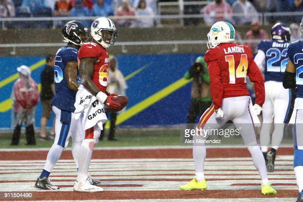 Delanie Walker of the Tennessee Titans celebrates his touchdown with Jarvis Landry of the Miami Dophins as Deion Jones of the Atlanta Falcons walks...