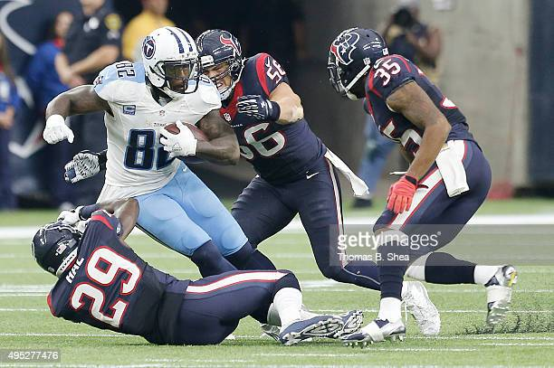 Delanie Walker of the Tennessee Titans is tackled by Andre Hal and Brian Cushing of the Houston Texans in the third quarter on November 1, 2015 at...