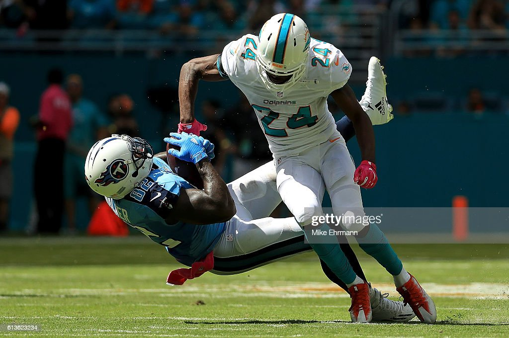 Delanie Walker #82 of the Tennessee Titans makes a catch over Isa Abdul-Quddus #24 of the Miami Dolphins during a game on October 9, 2016 in Miami Gardens, Florida.