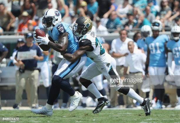 Delanie Walker of the Tennessee Titans runs with the football against Aaron Colvin of the Jacksonville Jaguars during the second half of their game...