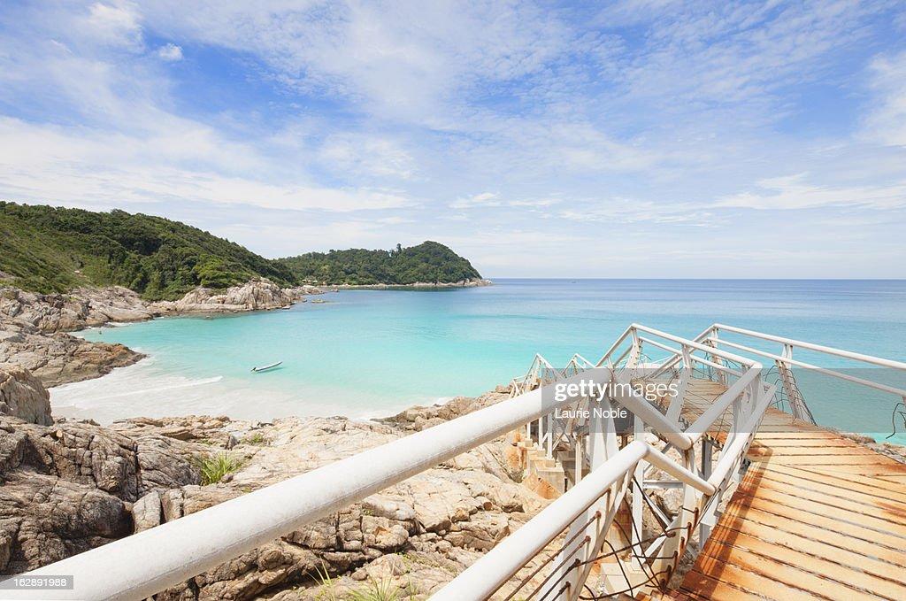 Delapidated pier leading to beach : Stock Photo