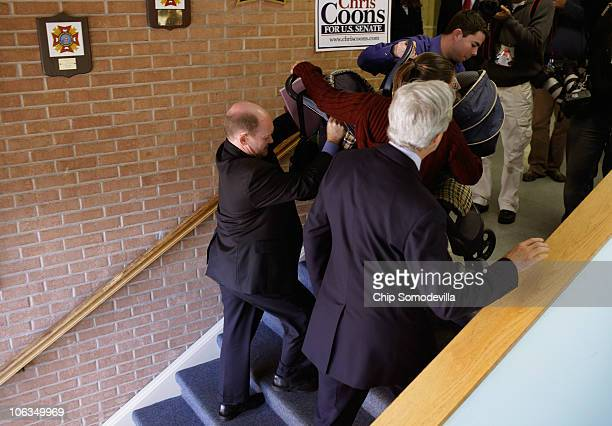 Delaware Democratic Senate nominee Chris Coons helps lift Pedro Colin Morales' stroller into the Veterans of Foreign Wars Post 475 before a campaign...