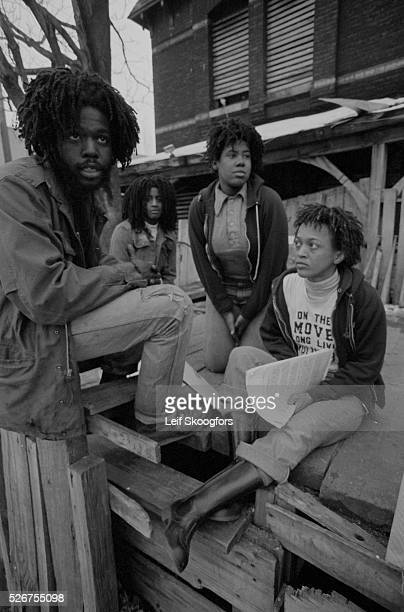 Delbert Africa and other members of MOVE a cult founded by John Africa sit in front of their barricaded house in the Powelton Village section of...