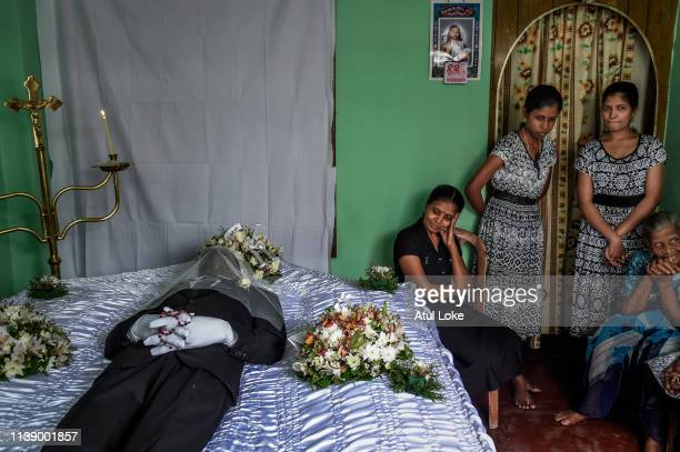 Delcia fernando mourns with her dauther in front of the body of the husband at house near St Anthony's Church on April 24 2019 in Colombo Sri Lanka...