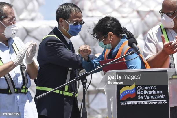 Delcy Rodriguez, Venezuela's vice president, center right, and Li Baorong, China's ambassador to Venezuela, bump elbows at a news conference in front...