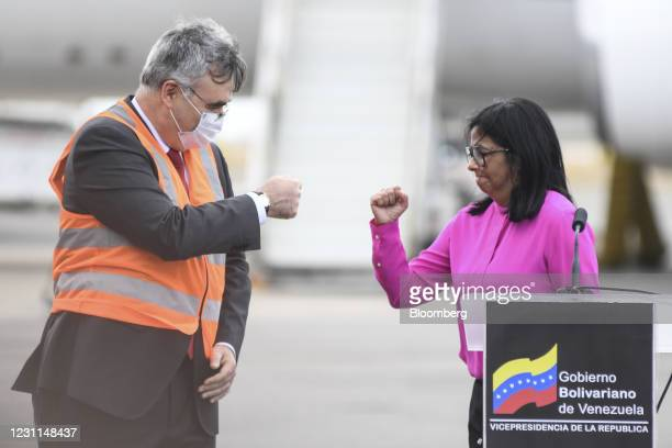 Delcy Rodriguez, Venezuela's vice president, right, fist bumps Sergey Melik-Bagdasarov, Russia's ambassador to Venezuela, during a press conference...