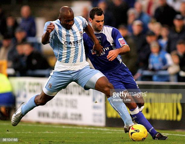 Dele Adebola of Coventry tackles Chris Barker of Cardiff during the CocaCola Championship match between Cardiff City and Coventry City at Ninian Park...