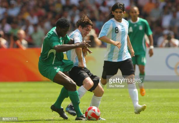 Dele Adeleye of Nigeria competes with Lionel Messi of Argentina in the Men's Gold Medal football match between Nigeria and Argentina at the National...