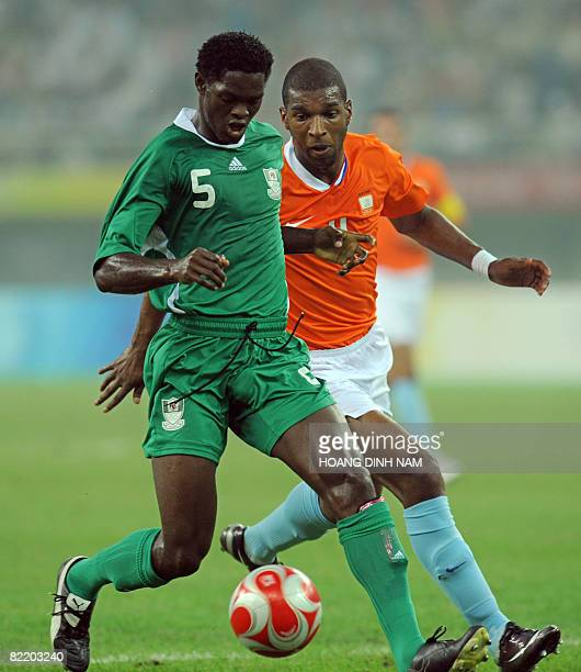 Dele Adeleye of Nigeria vies for the ball with Ryan Babel of the Netherlands during their 2008 Beijing Olympic Games first round group B men's...