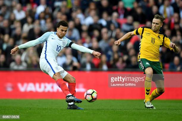 Dele Ali of England takes a shot at goal under pressure from Arturas Zulpa of Lithuania during the FIFA 2018 World Cup Qualifier between England and...