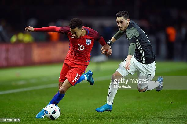 Dele Alli of England and Mesut Oezil of Germany compete for the ball during the International Friendly match between Germany and England at...