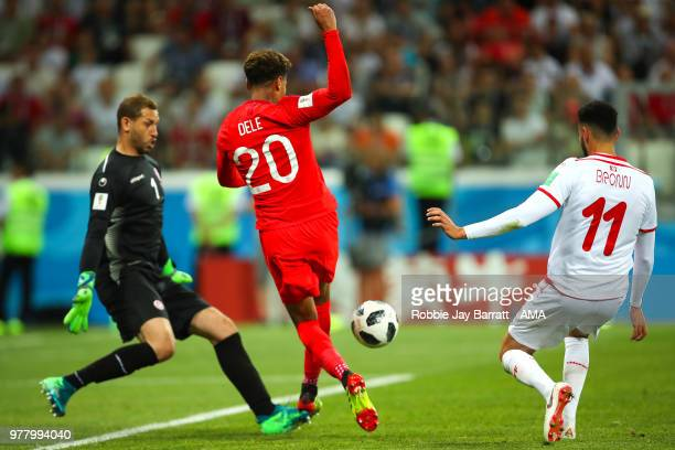 Dele Alli of England competes with Dylan Bronn and Farouk Ben Mustapha of Tunisia during the 2018 FIFA World Cup Russia group G match between Tunisia...