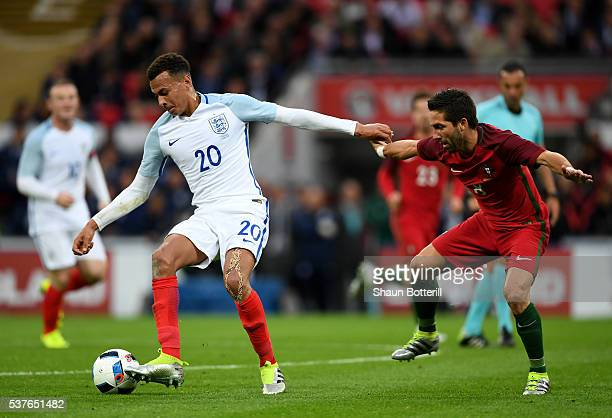 Dele Alli of England holds off Joao Moutinho of Portugal during the international friendly match between England and Portugal at Wembley Stadium on...