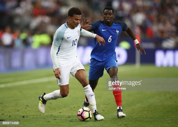 Dele Alli of England holds off Paul Pogba of France during the International Friendly match between France and England at Stade de France on June 13...