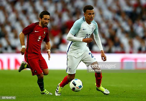 Dele Alli of England is chased by Joao Moutinho of Portugal during the international friendly match between England and Portugal at Wembley Stadium...