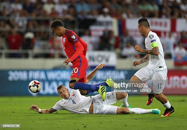 Dele Alli of England is tackled by Jan Durica of Slovakia during the 2018 FIFA World Cup Qualifier Group F match between Slovakia and England at City...