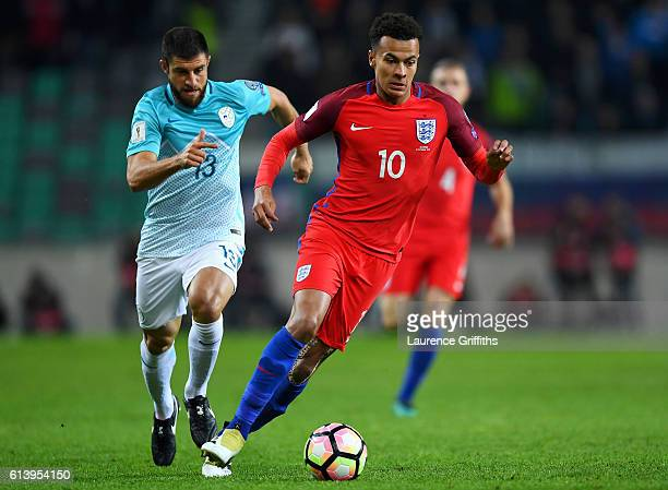 Dele Alli of England runs with the ball under pressure from Bojan Jokic of Slovenia during the FIFA 2018 World Cup Qualifier Group F match between...
