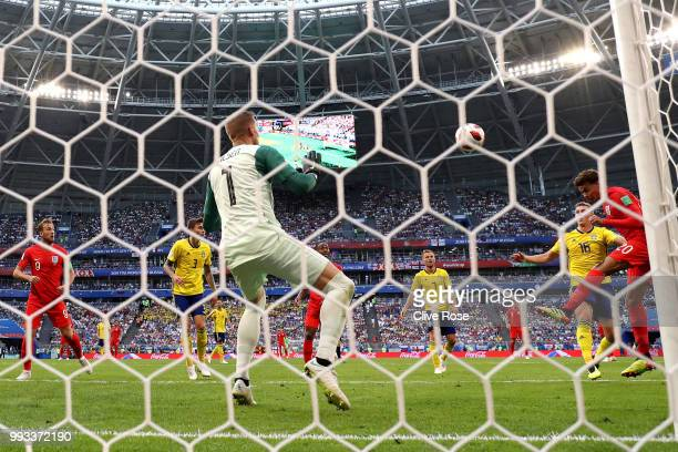 Dele Alli of England scores past Robin Olsen of Sweden his team's second goal during the 2018 FIFA World Cup Russia Quarter Final match between...