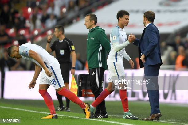 Dele Alli of England shakes hands with Gareth Southgate manager of England as he is substituted for Jake Livermore of England during the FIFA 2018...