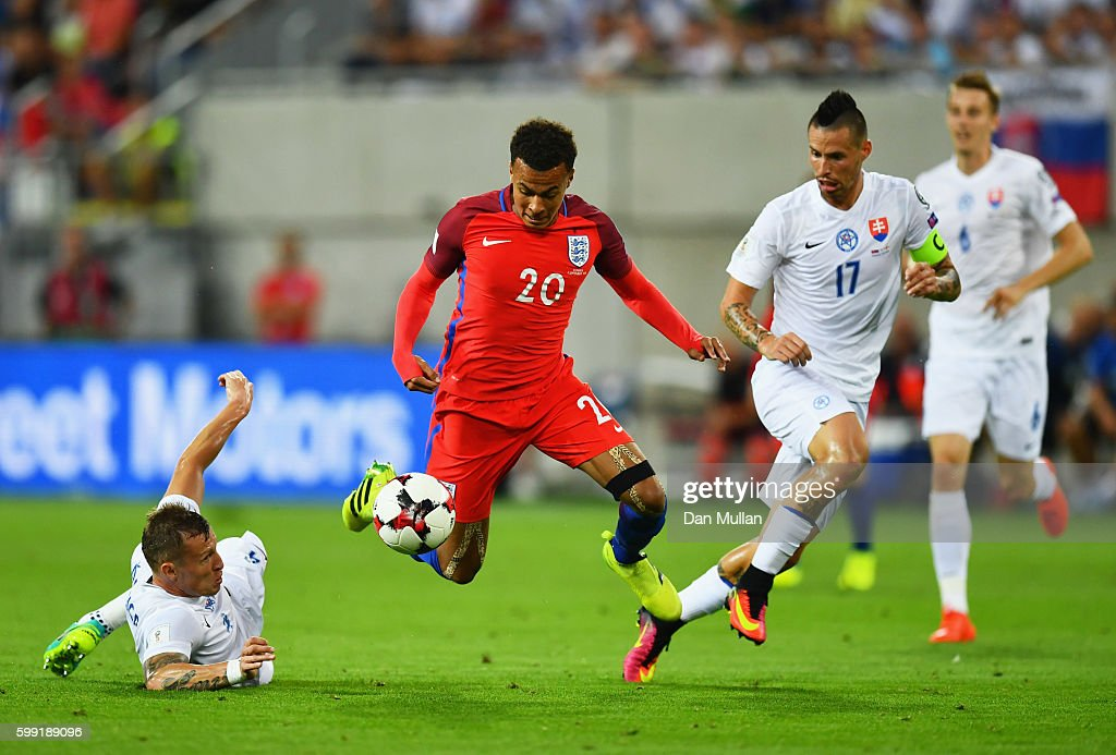 Dele Alli of England takes on Jan Durica (L) and Marek Hamsik of Slovakia (17) during the 2018 FIFA World Cup Group F qualifying match between Slovakia and England at City Arena on September 4, 2016 in Trnava, Slovakia.