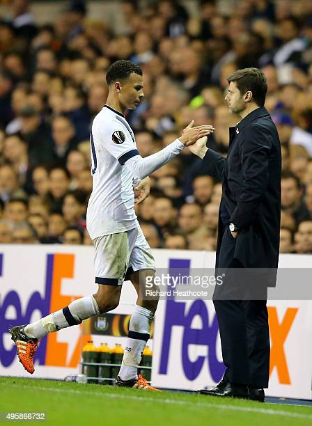 Dele Alli of Spurs shakes hands with Mauricio Pochettino the manager of Spurs as he is substituted in the second half during the UEFA Europa League...