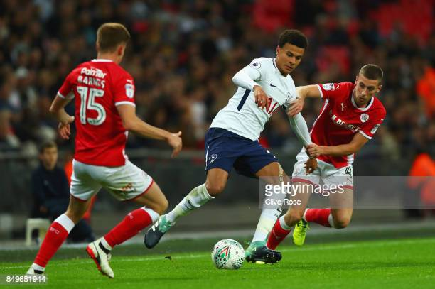 Dele Alli of Tottenham Hotspur and Joe Williams of Barnsley battle for possession during the Carabao Cup Third Round match between Tottenham Hotspur...