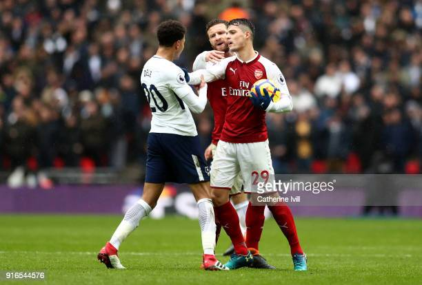 Dele Alli of Tottenham Hotspur argues with Shkodran Mustafi of Arsenal and Granit Xhaka of Arsenal during the Premier League match between Tottenham...