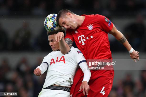 Dele Alli of Tottenham Hotspur battles for a header with Niklas Sule of FC Bayern Munich during the UEFA Champions League group B match between...