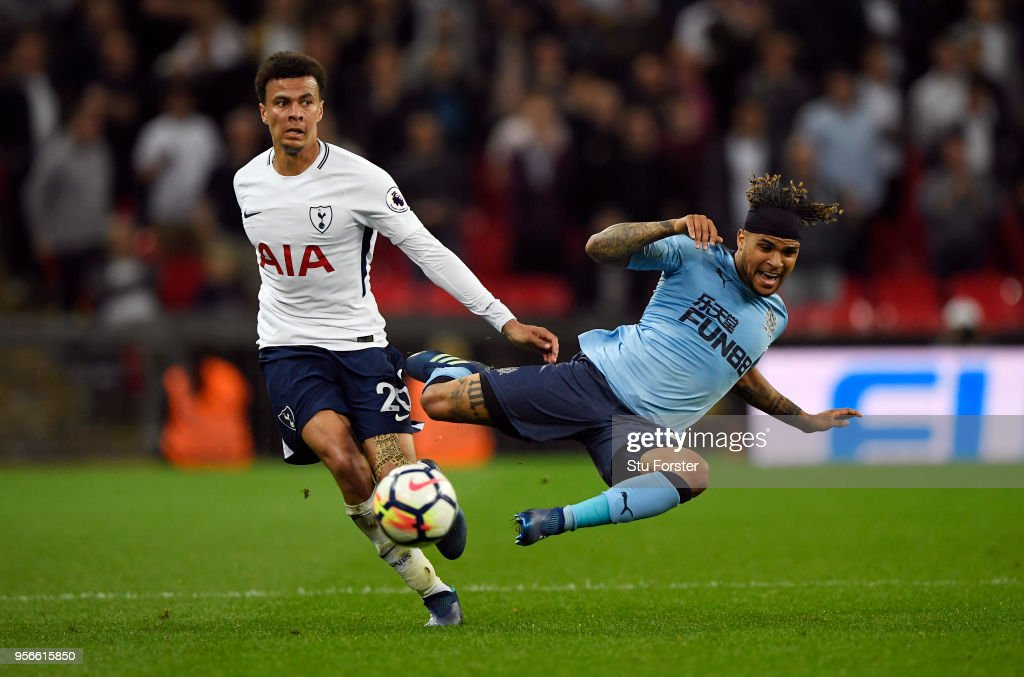 Dele Alli of Tottenham Hotspur battles for possession with Deandre Yedlin of Newcastle United during the Premier League match between Tottenham Hotspur and Newcastle United at Wembley Stadium on May 9, 2018 in London, England.