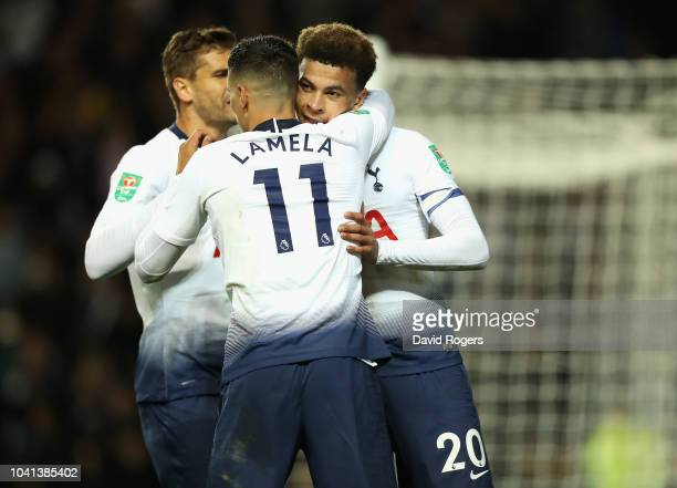 Dele Alli of Tottenham Hotspur celebrates with team mate Erik Lamela after scoring their first goal during the Carabao Cup Third Round match between...