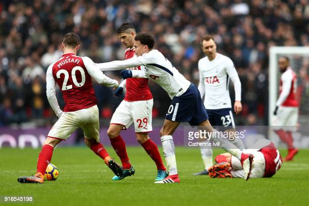 Dele Alli of Tottenham Hotspur clashes with Shkodran Mustafi of Arsenal during the Premier League match between Tottenham Hotspur and Arsenal at...