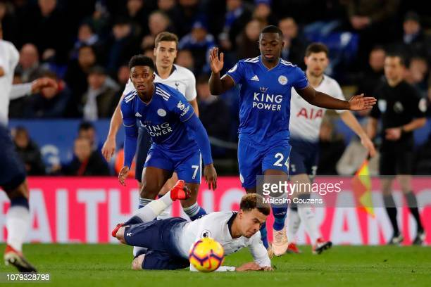 Dele Alli of Tottenham Hotspur falls under a challenge from Nampalys Mendy of Leivester City during the Premier League match between Leicester City...